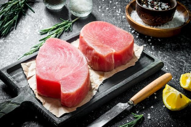 Сырое филе тунца на разделочной доске со специями и розмарином на темном деревенском столе