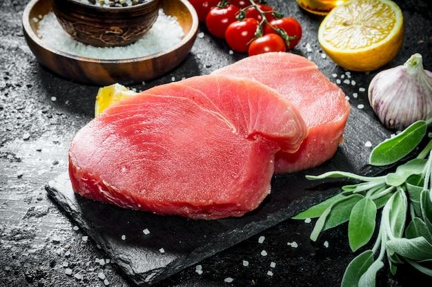 Сырое филе тунца на каменной доске с шалфеем и лимоном на деревенском столе