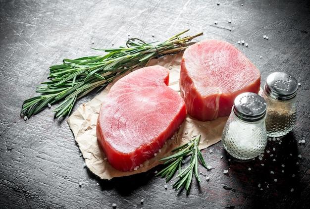 Сырое филе тунца на бумаге с розмарином и специями на темном деревенском столе.