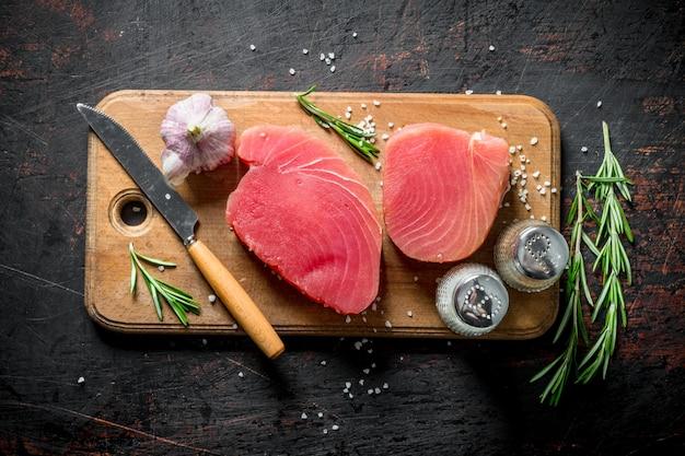 Сырое филе тунца с розмарином и специями. на темном деревенском