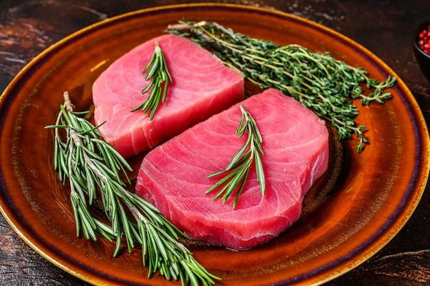Сырое филе тунца с розмарином и тимьяном на тарелке.