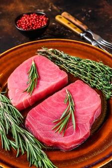 Сырое филе тунца с розмарином и тимьяном на тарелке