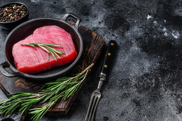 Сырое филе тунца с розмарином на сковороде