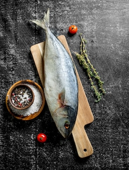Raw tuna fish on cutting board with thyme and spices on dark rustic table
