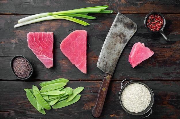 원시 참치 스테이크, 재료가 들어간 신선한 붉은 참치 필렛, 녹색 완두콩, 참깨와 향신료 세트, 오래된 정육점 칼, 오래 된 어두운 나무 테이블에