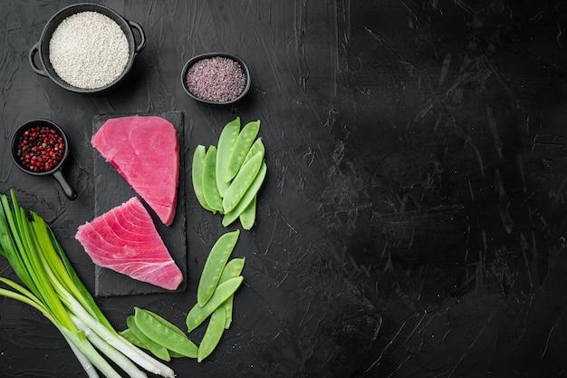 생 참치 스테이크, 재료가 들어간 신선한 붉은 참치 필레, 녹색 완두콩, 참깨 및 향신료 세트, 돌판에, 검은 돌에