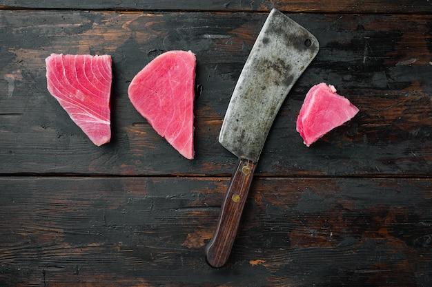Сырой стейк из тунца, набор свежего филе красного тунца и старый нож мясника на старом темном деревянном столе