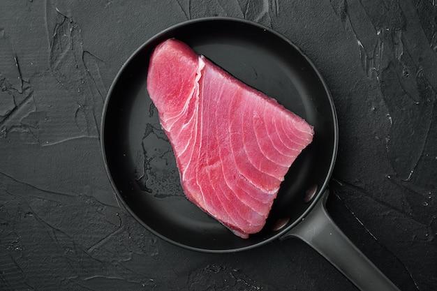 Сырой стейк из тунца, набор свежего филе красного тунца, на чугунной сковороде, на черном камне