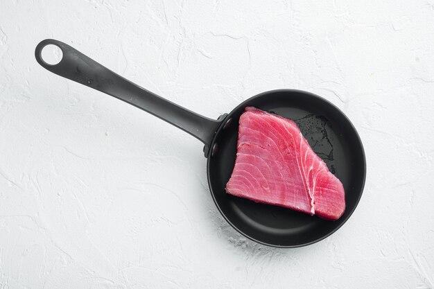 Сырой стейк из тунца, набор свежего филе красного тунца, на сковороде, на белом камне