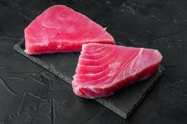 Сырой стейк из тунца, набор свежего филе красного тунца, на каменной доске, на черном камне