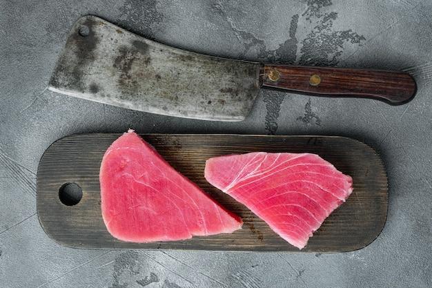 Сырой стейк из тунца, набор свежего филе красного тунца на деревянной разделочной доске и старый нож мясника на сером камне