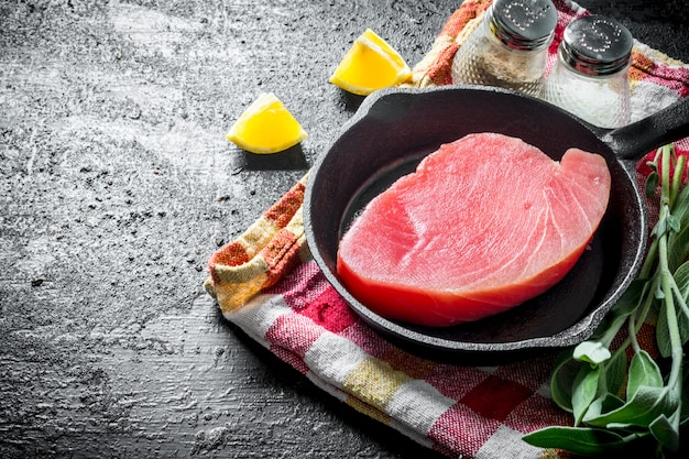 Сырой стейк из тунца на сковороде на салфетке с шалфеем, специями и дольками лимона на черном деревенском столе.