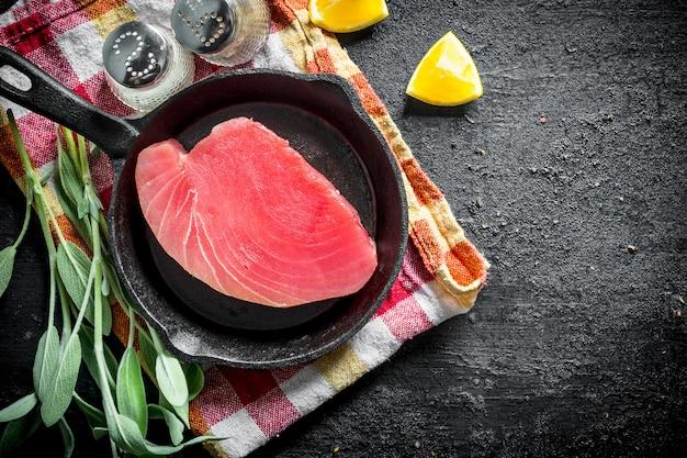 黒い素朴なテーブルの上にサルビア、スパイス、レモンスライスとナプキンの鍋で生マグロステーキ