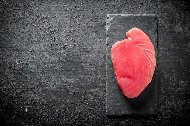 Стейк из сырого тунца на каменной доске. на черном деревенском фоне