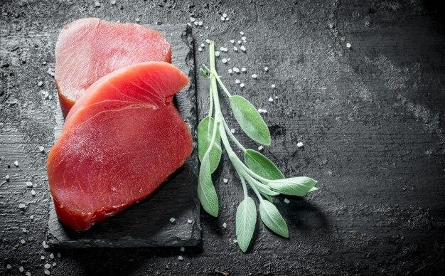 石板に生のマグロのステーキ、スパイス、サルビア、レモンスライス。