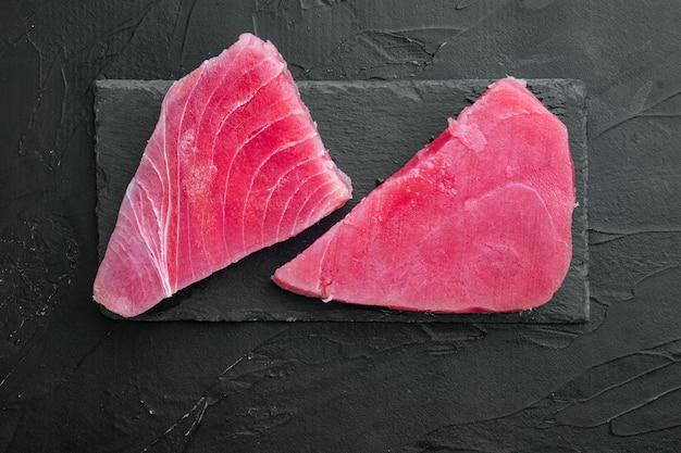 Набор сырого стейка из тунца, на каменной доске, на черном камне