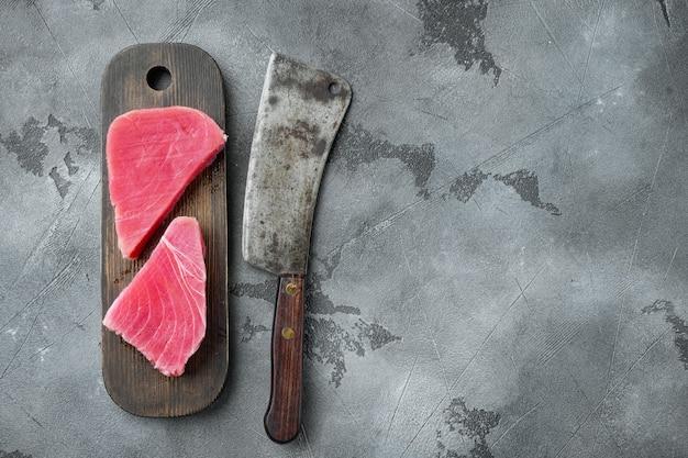 Набор сырого стейка из тунца на деревянной разделочной доске и старый нож мясника на сером камне