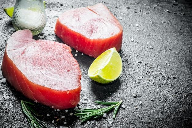 Сырой стейк из тунца с розмарином, лаймом и солью. на черном деревенском фоне