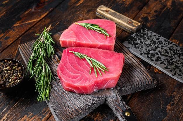 Сырые стейки тунца на деревянной разделочной доске с тесаком.