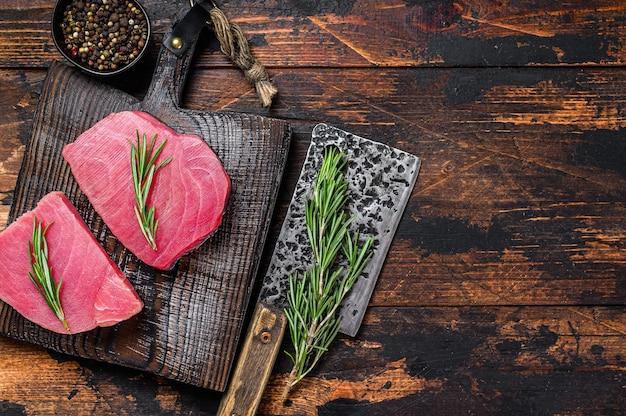 Сырые стейки тунца на деревянной разделочной доске с тесаком