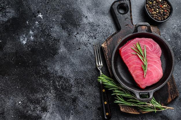 Сырые стейки тунца на столе