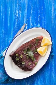 Сырой тунец с лимоном и лавровым листом на керамике