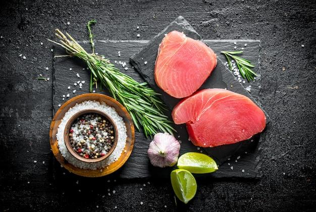 Сырой тунец с розмарином, чесноком, лаймом и специями. на черном деревенском фоне