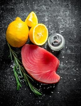 Сырой тунец с нарезанным лимоном, веточкой розмарина и солью. на темном деревенском