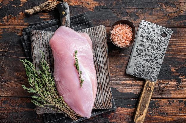 肉切り包丁が付いている木の肉屋の板の生の七面鳥の胸の切り身。ダークウッドのテーブル。上面図。