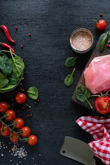 生の七面鳥の切り身を焼く準備ができています。チェリートマト、唐辛子、ほうれん草の葉、緑の木製のまな板の上の鶏の切り身。コピースペース。上面図。縦写真