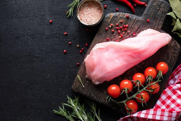 生の七面鳥の切り身を焼く準備ができています。チェリートマト、唐辛子、ほうれん草の葉、緑の木製のまな板の上の鶏の切り身。コピースペース。上面図