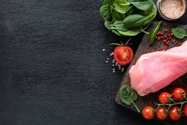 Raw turkey fillet ready for grilling. chicken fillet on a wooden cutting board with cherry tomatoes, hot pepper, spinach leaves and greens. copy space. top view