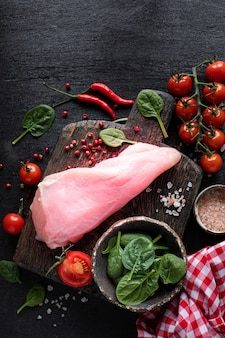 Raw turkey fillet ready for grilling. chicken fillet on a wooden cutting board with cherry tomatoes, hot pepper, spinach leaves and greens.