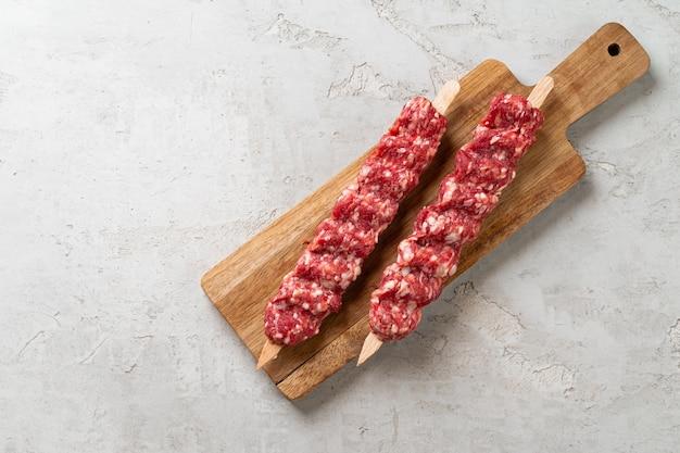 テーブルの上の生のトルコの伝統的な肉のケバブ。閉じる。