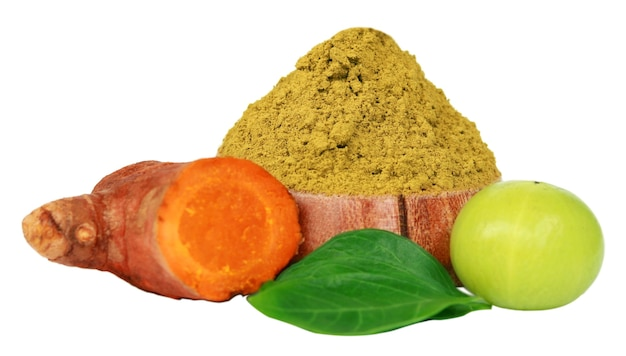 Raw turmeric and amla with henna powder and green leaves over white background
