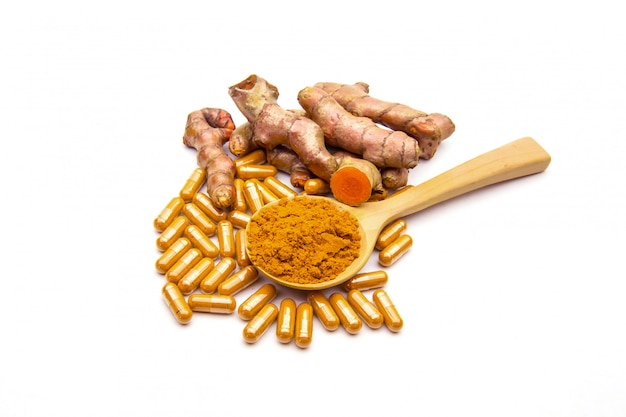 Raw turmeric,capsules and powder in a wooden spoon.