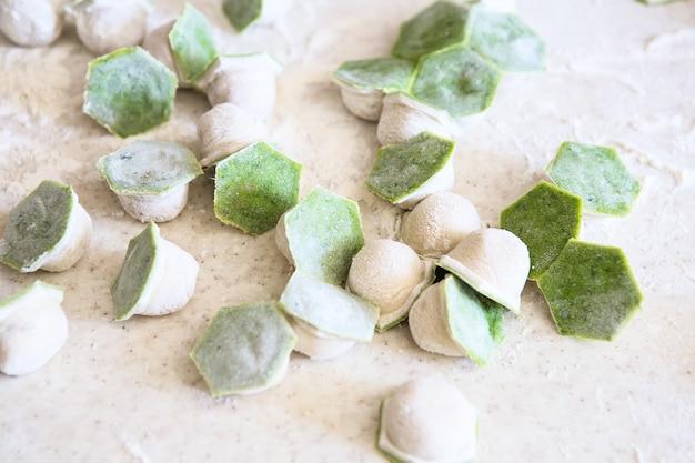 ほうれん草、チーズ、または小麦粉とテーブルの上の肉と生のツートンカラーの白と緑の餃子