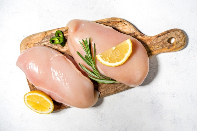 흰색 요리 테이블 배경에 향신료와 요리를 위한 재료와 향신료를 넣은 익히지 않은 닭 가슴살 필레