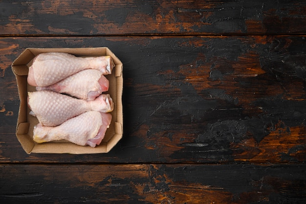 Raw and uncooked chicken drumsticks set, in paper pack, on old dark wooden table, top view flat lay