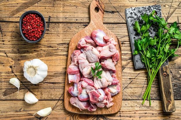 Сырые сырые куриные желудки, желудок на разделочной доске.