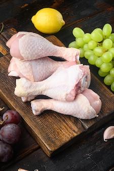 원시 생 닭 다리, 재료 세트, 포도와 파슬리, 나무 커팅 보드, 오래 된 어두운 나무 테이블에 나지만