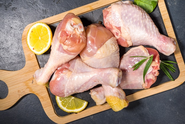 生の未調理の鶏の脚、調理用のスパイスとハーブが入ったバチ、黒いテーブルの背景上面図のコピースペース