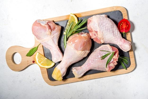 生の未調理の鶏の脚、調理用のスパイスとハーブが入ったバチ、白いテーブルの背景上面図のコピースペース