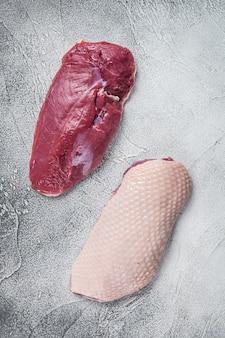 Сырые сырые стейки филе утиной грудки на столе мясника. белый стол. вид сверху.