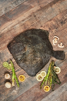 Raw uncooked flatfish with lemons, asparagus, herbs, mushrooms and spices on wooden table. european plaice, top view