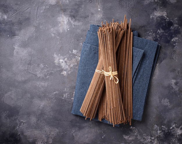 Raw uncooked japanese soba noodles on grey bacground