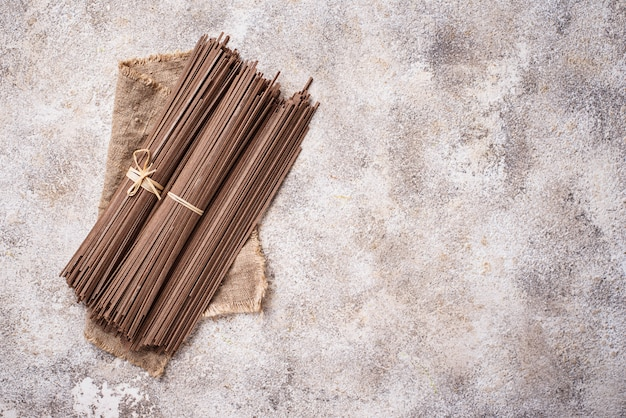 Raw uncooked japanese soba noodles on light bacground