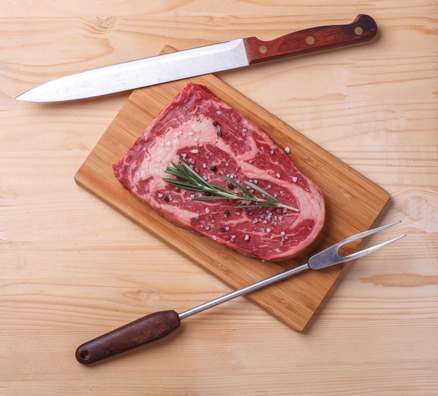 木製の机の上にローズマリー、ナイフ、クックフォークを添えた生の未調理の霜降りステーキリブアイ