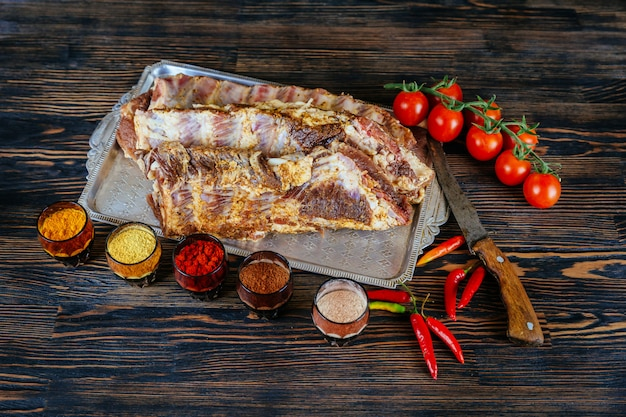 Raw uncooked pork ribs on wooden cut board ready to cook black textured.