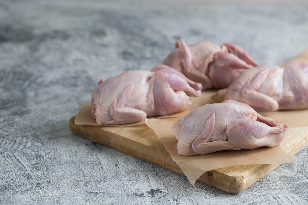 Raw uncooked quail. raw meat quails ready for cooking on a cutting board with copy space